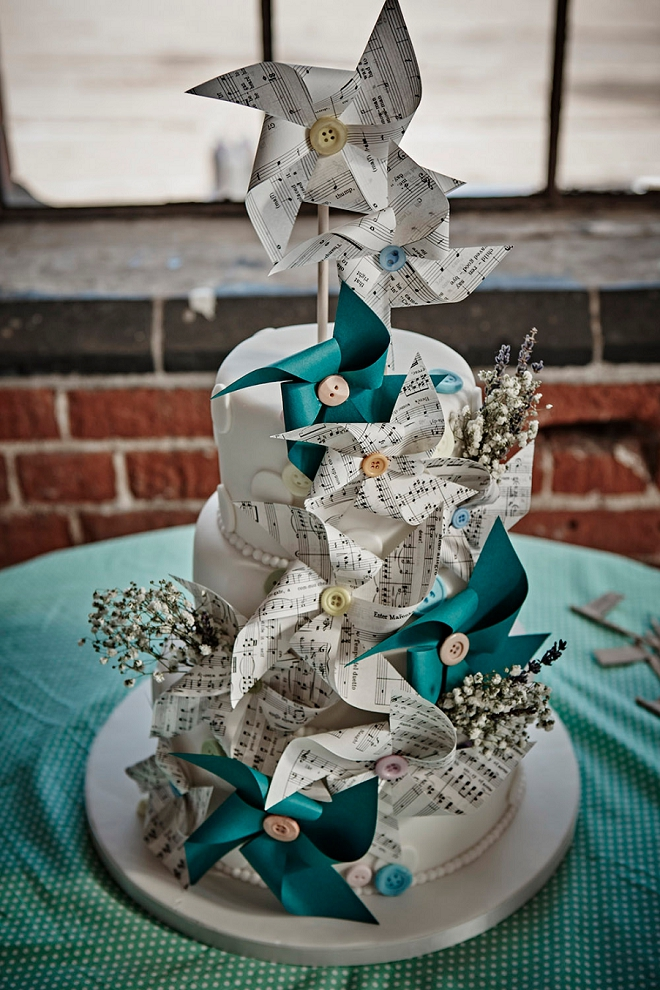 We're loving this gorgeous cake and DIY pinwheels out of music paper this fun Bride DIY'd for her UK wedding!!