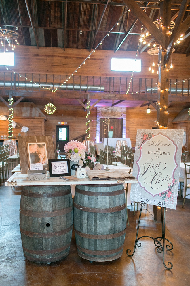 How darling is this couple's reception welcome table with whiskey barrels?!