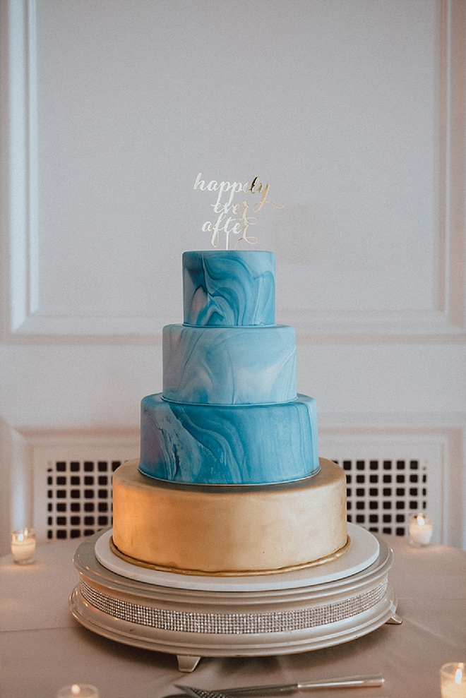 Swooning over this statement ombre blue wedding cake with gold cake topper!