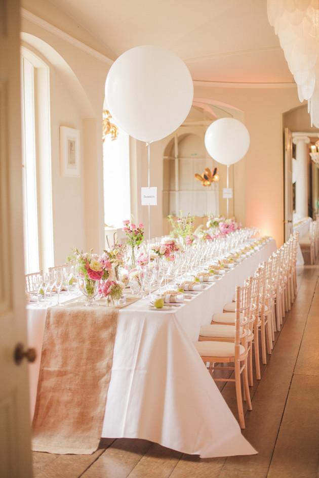 Tão elegante. Casamento rosa com balões brancos como números de mesa.