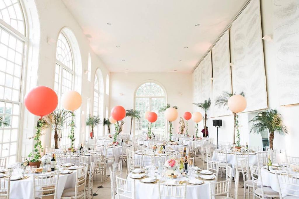 Tropical palm tree wedding! Love the balloons used as table numbers and the coral.