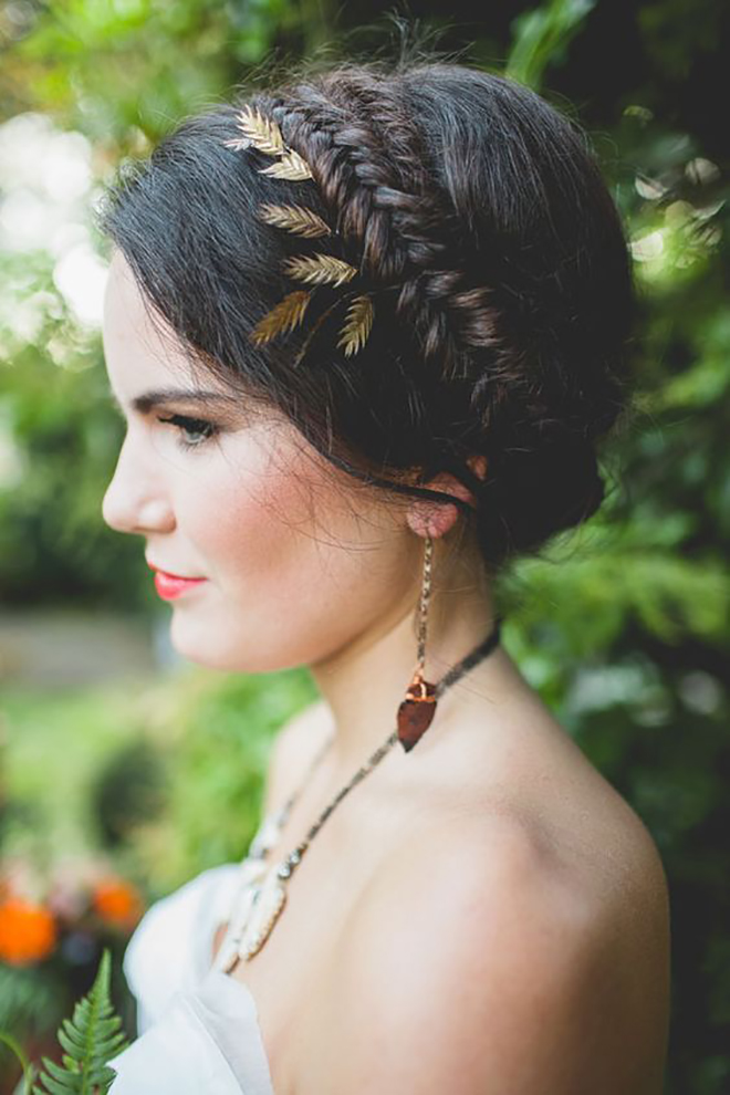 A braided crown with dainty leaves is a great winter wedding hair idea.