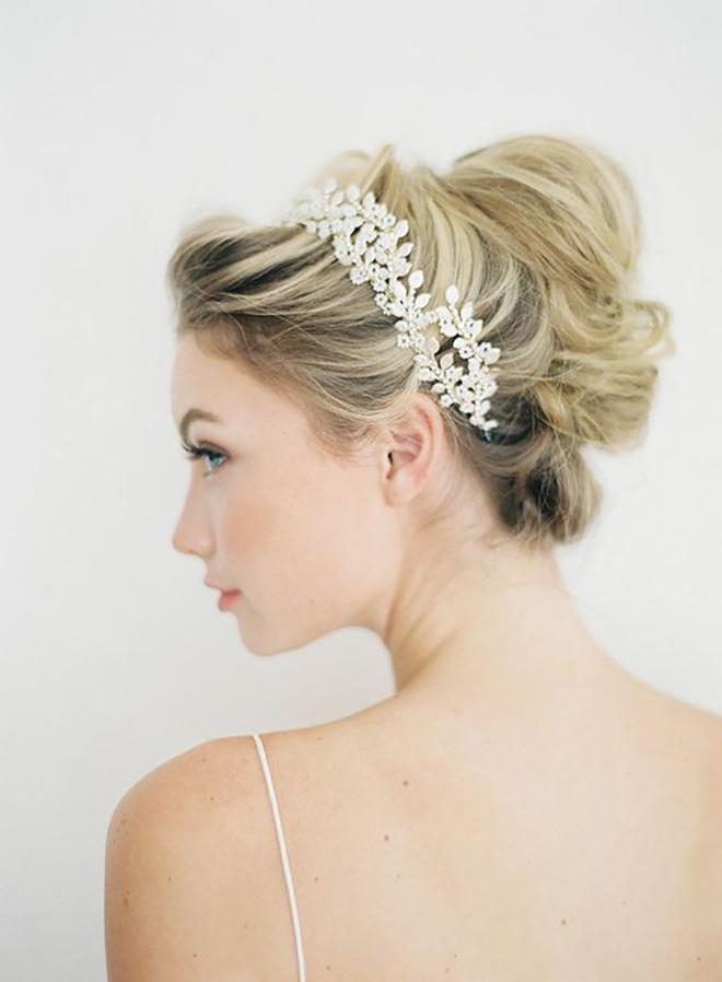 A high messy bun is a great idea for winter wedding hair.