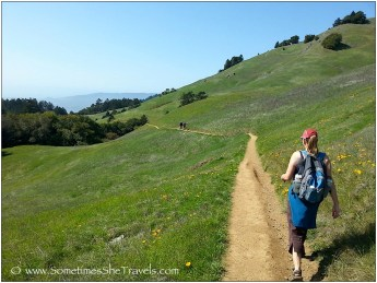 woman walking on trail in green hills