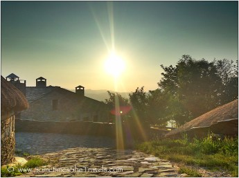 Sun setting over old stone houses and cobblestone street