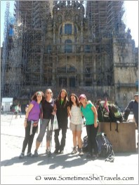One man and four women with backpacks in front of the Cathedral of Santiago