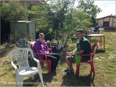 Man and woman on red plastic chairs in garden