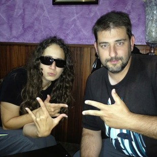 Woman in glasses next to man making rapper signs