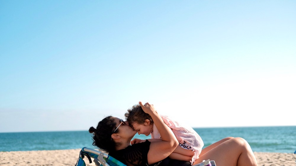 mother kissing toddler at the beach