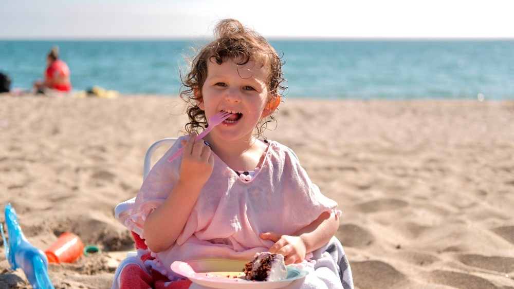 cute toddler at the beach eating cake