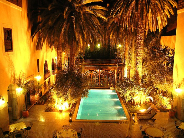 Moroccan Riad courtyard and pool at night, huge palm trees, Photo: Flickr