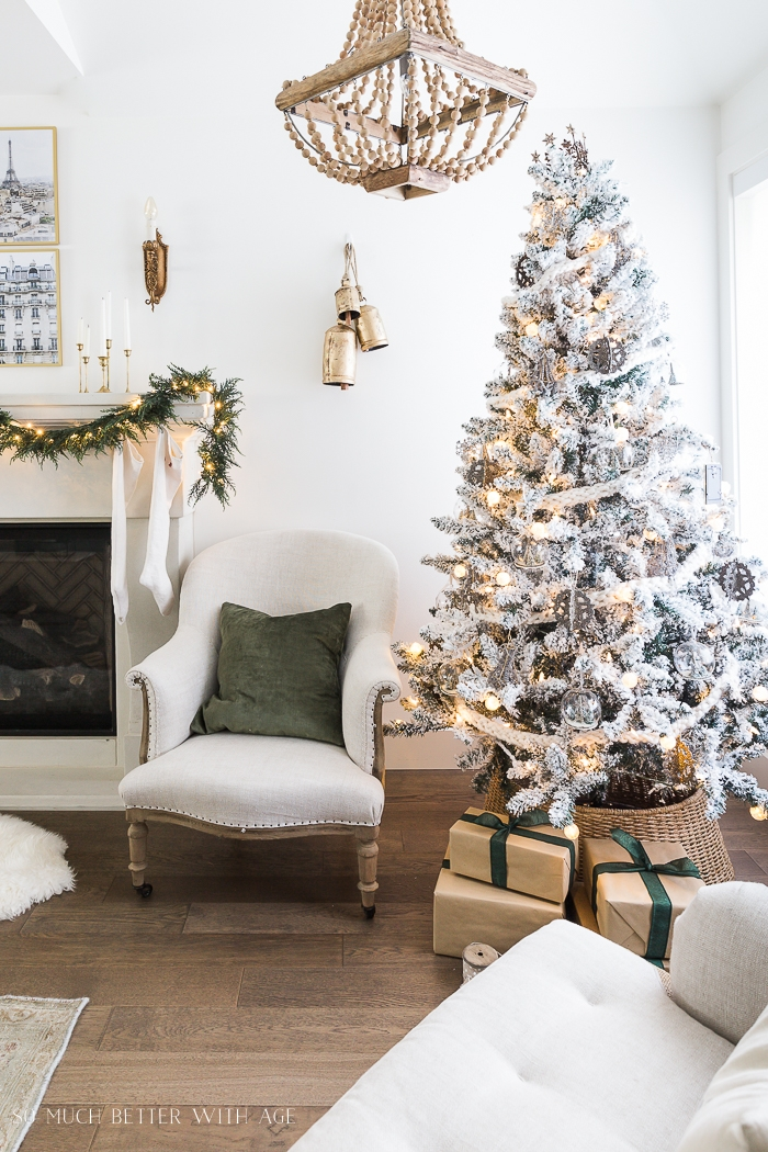 Christmas tree with presents with a chair and green pillow next to it.