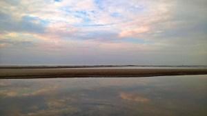 Wolken spiegeln sich im Priel