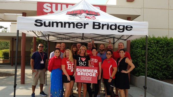 Staff gather a Summer Bridge tent holding a sign.