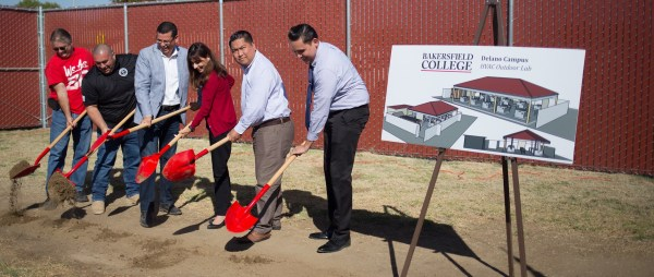 Faculty, staff, Pres. Christians and honored guests dig with red shovels.