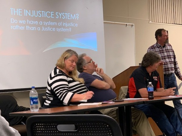 "Panel in front of the screen that says ""The Injustice System? Do we have a system of injustice rather than a Justice system?"""