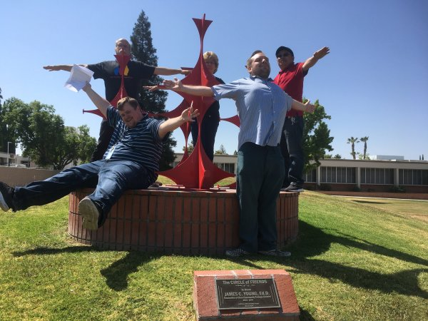 5 people with arms held out like the sculpture.