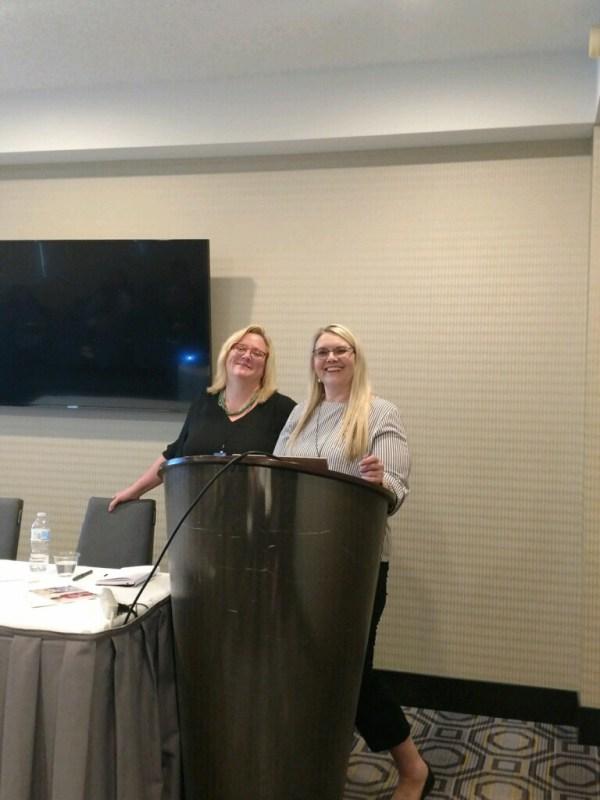 2 women at a podium.