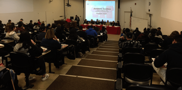 A full audience for the panel with Juvenile Justice slide behind them.