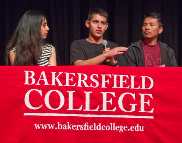 BC Dreamer student speaks with microphone, 2 panelists looking at him.