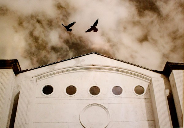 Black and white image of two black birds flying over a church-like building against a cloudy sky.