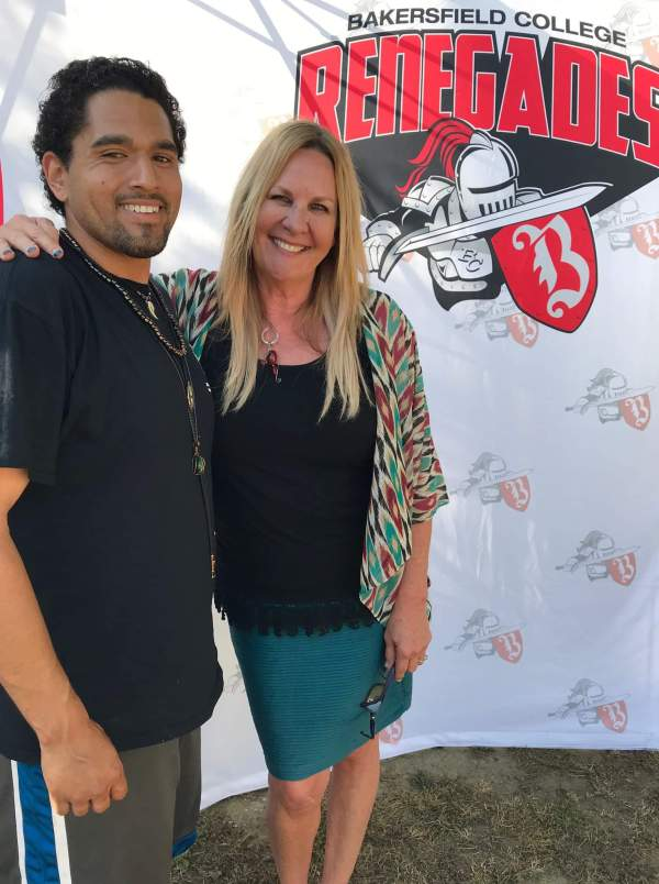 Posed in front of a Bakersfield College Renegades logo backdrop.