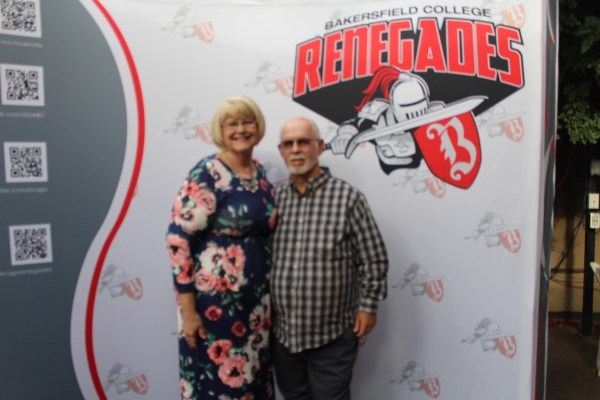 An older couple in front of the Renegade logo backdrop.