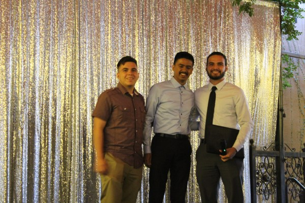 3 males pose in front of shimmery curtain.