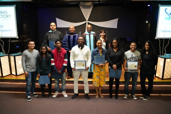 8 students with pastors and Sonya behind them hold up certificates.