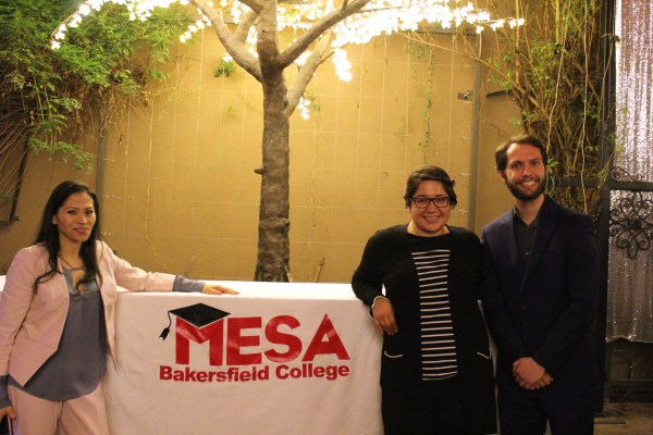 Connie, a female and a male stand next to a table with MESA Bakersfield College logo.