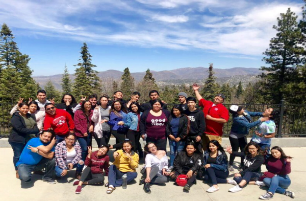 Group of students with forest trees and mountains in background.