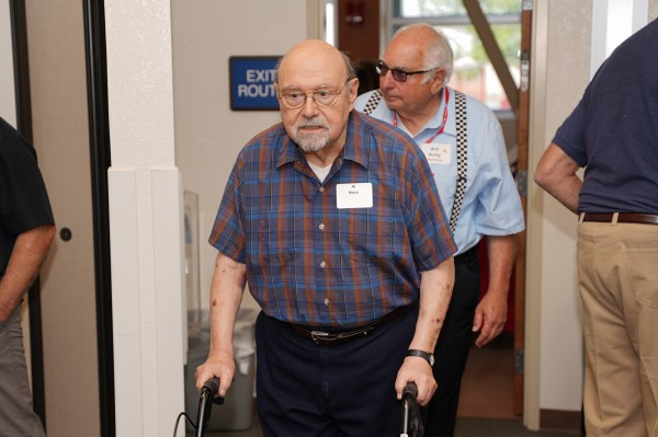 eldery man using walker entering room