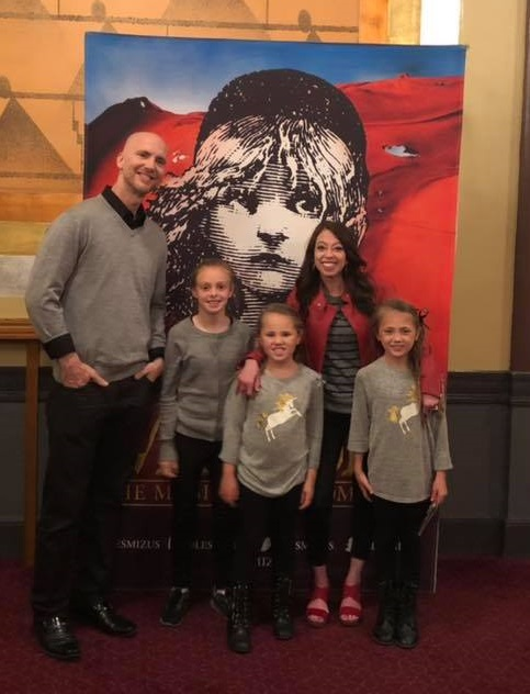 The Garrett family poses in front of the Les Mis poster