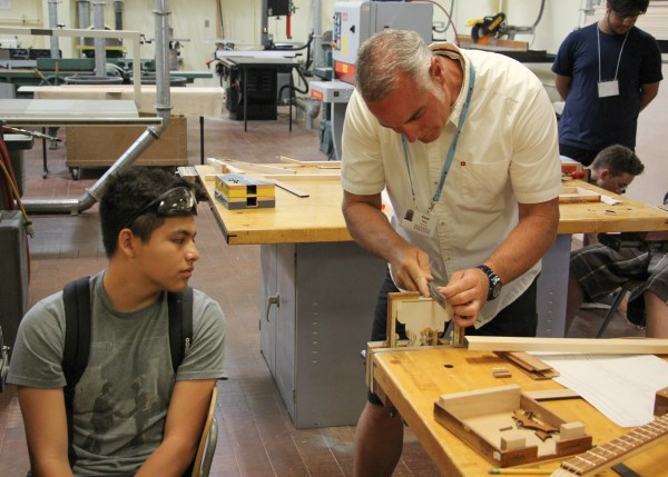 Martin Perez showing a student how to construct the guitar.
