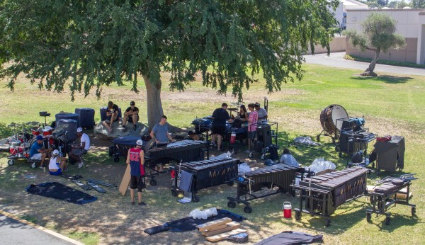 Students setting up drum sets in the shade of a tree.