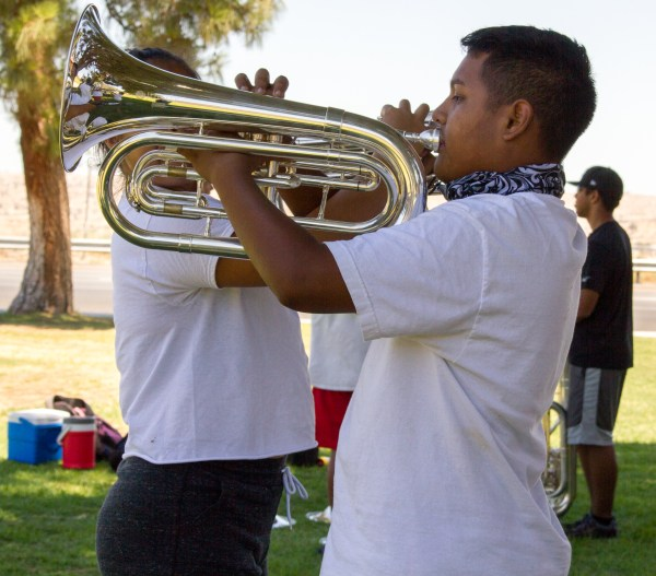 Tuba players practicing in the shade.
