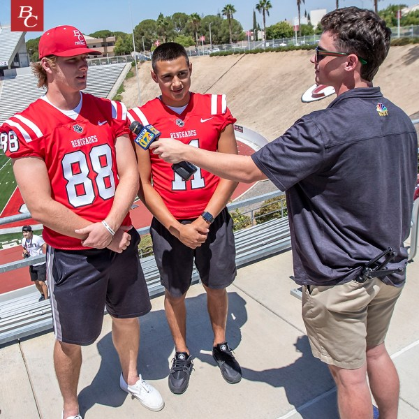 Football players being interviewed by news anchor.