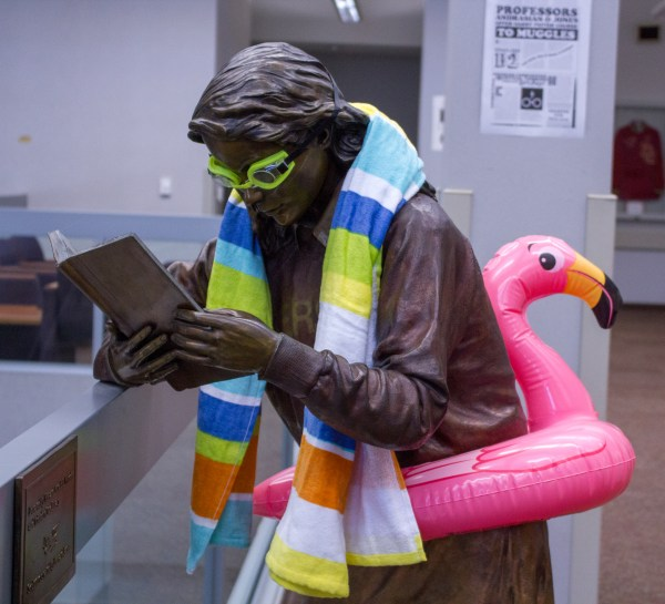 Statue of female student reading dressed with goggles, beach towel and flamingo float.
