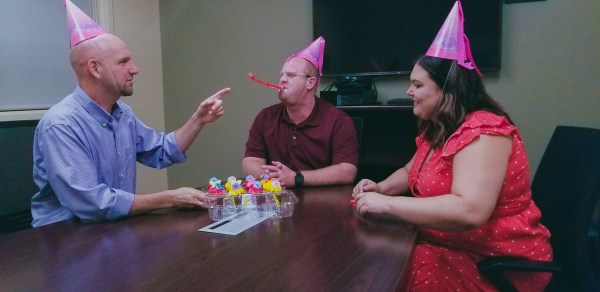 Todd, Bill and Tamara with party hats and cupcakes.