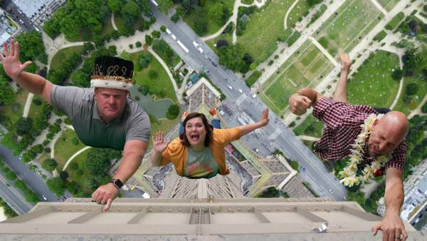 Bill and Todd holding on to the Eiffel tower and Tamara falling.