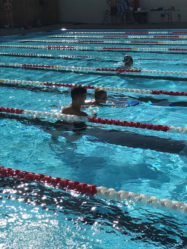 Student learning to swim with kick board.