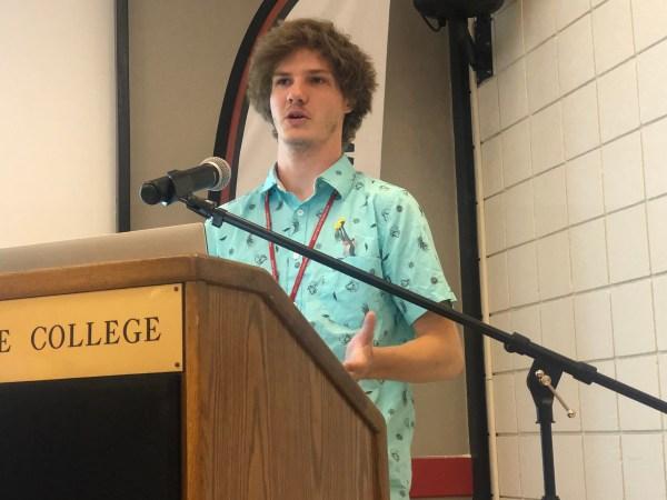 Speaks at the podium.