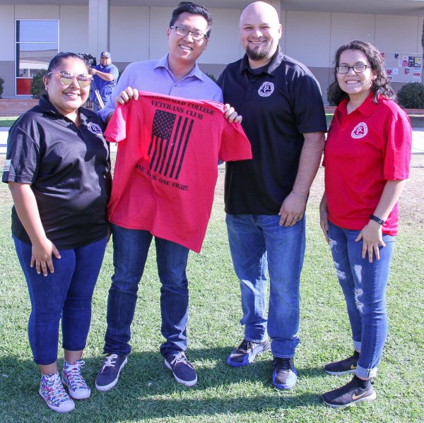 Vince holding a Veterans Club t-shirt.