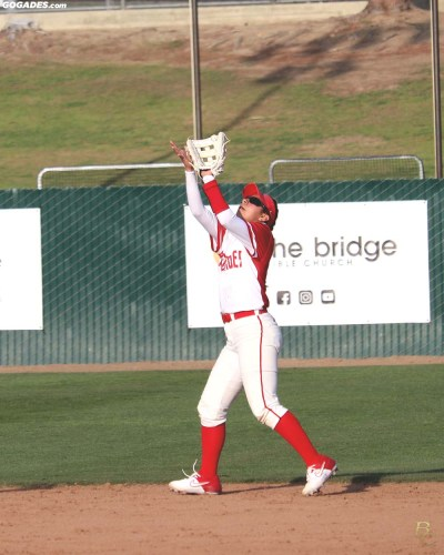 Female athlete catching fly ball.