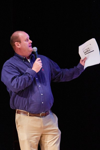 Bill Potter in blue shirt and khakis with paper in left hand.