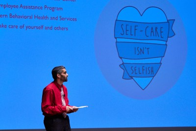 Nicky in front of the slide that says Self-care isn't selfish.