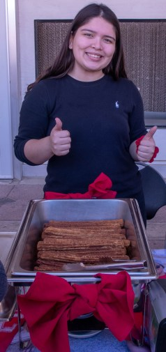Samantha with thumbs up behind a tray of churros.