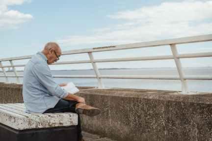 serious senior man reading book near fence on waterfront
