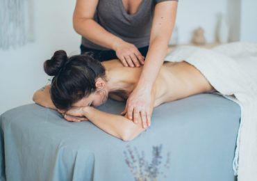 woman-lying-on-bed-while-having-a-massage-3865792