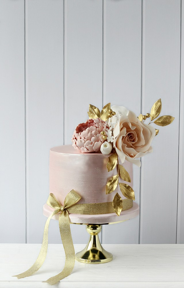 shimmery pale pink single tier celebration cake with pale pink flowers and gold foliage